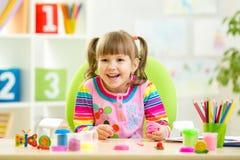 使用与五颜六色的黏土的微笑的孩子 库存图片