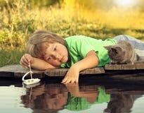 使用与从码头的一条小船的男孩和他心爱的小猫在池塘 图库摄影