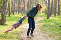 使用与他的女儿的愉快的母亲在公园在夏日 免版税库存图片