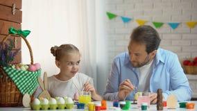 使用与他的小女儿的爸爸绘她的与油漆刷,乐趣的鼻子 影视素材