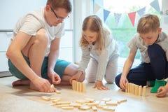 使用与他的有木块的两个逗人喜爱的孩子的年轻愉快的父亲 免版税库存图片