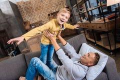 使用与他的沙发的父亲的快乐的男孩 免版税库存照片