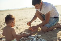 使用与他的沙子的儿子的年轻父亲在海滩 免版税库存照片