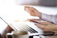 使用与信用卡的人流动付款为在膝上型计算机背景的网上购物 库存照片