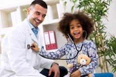 使用与儿科医生的微笑的非洲女孩 库存图片