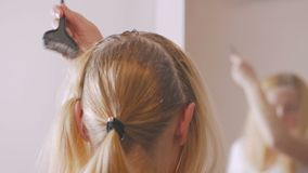 使用与刷子的漂白的油妇女在家照亮她的头发根 影视素材