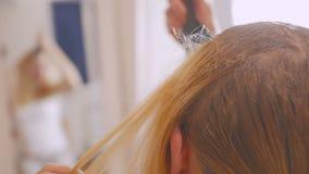 使用与刷子的漂白的油妇女在家照亮她的头发根 股票视频