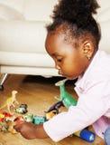 使用与动物玩具的小逗人喜爱的非裔美国人的女孩在ho 免版税图库摄影