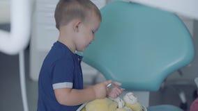 使用与医疗工具的可爱的小男孩坐在椅子在牙医办公室 无忧无虑儿童参观 股票录像