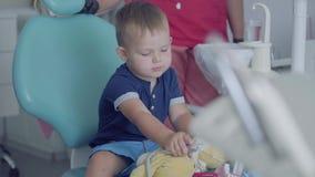 使用与医疗工具的可爱的小男孩坐在椅子在牙医办公室 无忧无虑儿童参观 股票视频