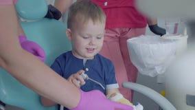 使用与医疗工具的可爱的小男孩坐在椅子在牙医办公室 无忧无虑的儿童参观的医生 股票录像