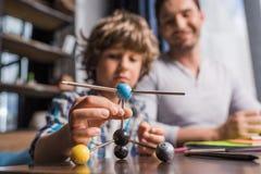 使用与原子模型的父亲和儿子 免版税库存照片