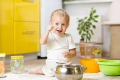 使用与厨具和粮食的小孩男孩在国内厨房里 免版税库存图片