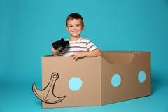 使用与双筒望远镜和纸板小船的逗人喜爱的小男孩 库存照片