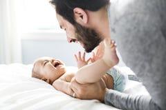 使用与可爱的婴孩的愉快的父亲在卧室 免版税图库摄影