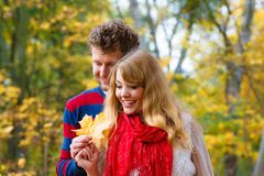 使用与叶子的夫妇在秋天公园 免版税库存图片