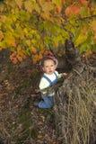 使用与叶子的小男孩在秋天公园 库存照片
