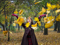 使用与叶子的少妇在秋天公园 库存照片