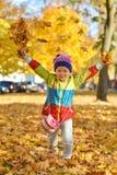 使用与叶子的明亮的衣裳的愉快的小女孩在一个城市公园在秋天 库存图片