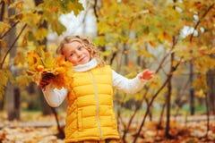 使用与叶子的逗人喜爱的小孩女孩在步行的秋天公园 免版税库存图片
