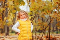 使用与叶子的逗人喜爱的小孩女孩在步行的秋天公园 库存图片