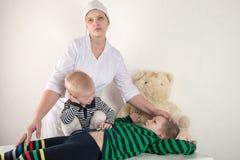 使用与听诊器在医生办公室,拥抱长毛绒玩具熊和微笑对照相机的愉快的逗人喜爱的男孩 女性小儿科 库存图片