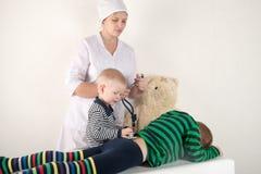使用与听诊器在医生办公室,拥抱长毛绒玩具熊和微笑对照相机的愉快的逗人喜爱的男孩 女性小儿科 免版税图库摄影