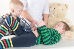 使用与听诊器在医生办公室,拥抱长毛绒玩具熊和微笑对照相机的愉快的逗人喜爱的男孩 女性小儿科 免版税库存照片