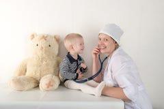 使用与听诊器在医生办公室,拥抱长毛绒玩具熊和微笑对照相机的愉快的逗人喜爱的男孩 女性小儿科 复制 免版税图库摄影