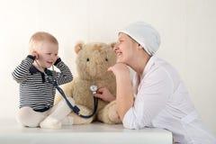 使用与听诊器在医生办公室,拥抱长毛绒玩具熊和微笑对照相机的愉快的逗人喜爱的男孩 女性小儿科 复制 免版税库存图片