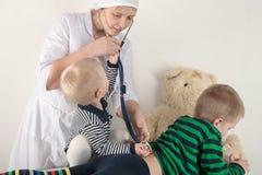 使用与听诊器在医生办公室,拥抱长毛绒玩具熊和微笑对照相机的愉快的逗人喜爱的男孩 女性小儿科 复制 库存图片