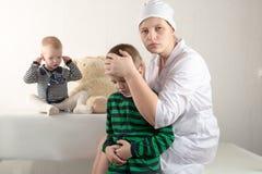 使用与听诊器在医生办公室,拥抱长毛绒玩具熊和微笑对照相机的愉快的逗人喜爱的男孩 女性小儿科 复制 免版税库存照片