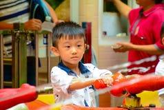 使用与喷水的亚裔中国男孩 免版税库存照片