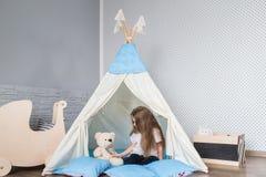 使用与圆锥形帐蓬帐篷的孩子 免版税库存图片