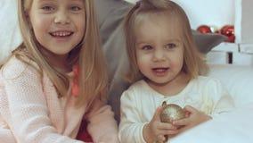 使用与圣诞节球的两个妹,当坐长沙发时 免版税库存照片