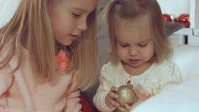 使用与圣诞节球的两个妹,当坐长沙发时 库存照片