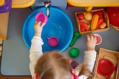 使用与在一个小玩具厨房的玩具的女孩 免版税库存照片