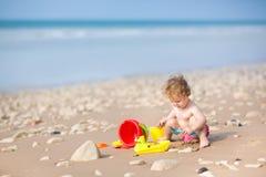 使用与在一个美丽的海滩的沙子的逗人喜爱的女婴 图库摄影