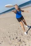 演奏飞碟的健康资深妇女在海滩 免版税库存图片