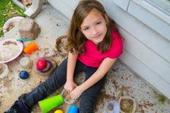 使用与在一张杂乱土壤微笑的画象的泥的女孩 库存照片