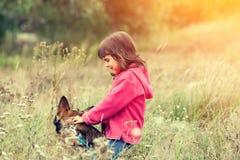 使用与在一棵高草的狗的小女孩 库存照片