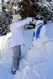 使用与在一次多雪的胜利的一个雪人的愉快的微笑的十几岁的女孩 免版税库存图片
