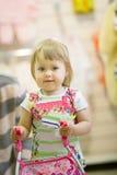 使用与在一件明亮的礼服的一辆婴儿推车的愉快的小女孩 库存照片