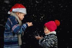 使用与在冬天步行的雪花的愉快的孩子 免版税图库摄影