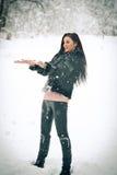 使用与在冬天风景的雪的观点的愉快的深色的女孩 冬天背景的美丽的年轻女性 可爱的妇女 免版税图库摄影