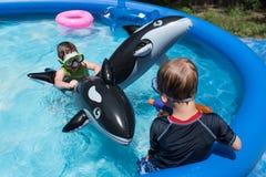 使用与在后院游泳池的浮游物的两个男孩 免版税库存图片