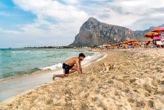 使用与在圣维托洛卡波海滩的一条狗的年轻人在一多云天 图库摄影