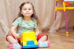 使用与在地板上的一辆玩具汽车的儿童女孩 库存图片