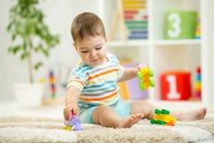 使用与在地板上的五颜六色的塑料砖的愉快的婴孩 获得乐趣和制造火车的小孩在建设者外面 库存图片
