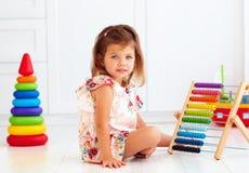 使用与在地板上的木玩具的逗人喜爱的矮小的女婴 库存照片
